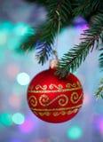 Bola de la Navidad con la ejecución del ornamento en el árbol de Navidad, luces defocused Imagen de archivo
