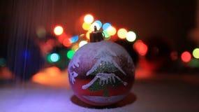 Bola de la Navidad con los ornamentos en el paisaje Nevado de la Navidad almacen de metraje de vídeo