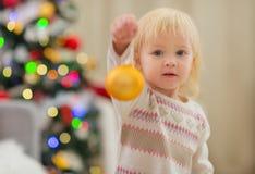 Bola de la Navidad de la explotación agrícola del bebé cerca del árbol de navidad Foto de archivo libre de regalías