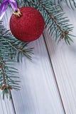 Bola de la Navidad de la imagen de Copyspace en los tableros blancos y la rama del perno imagen de archivo