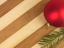 Bola de la Navidad de la tabla de cortar de dos tonos y ramita del pino Imagen de archivo libre de regalías