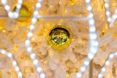 Bola de la Navidad del oro con la reflexión de la escama de la nieve Foto de archivo libre de regalías