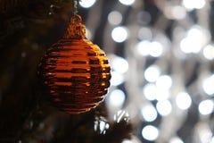 Bola de la Navidad del oro en árbol con las luces de la Navidad Imagen de archivo libre de regalías