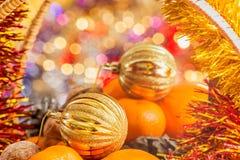 Bola de la Navidad del oro en la cesta con las frutas y las nueces Fotos de archivo libres de regalías