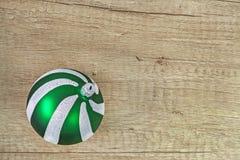 Bola de la Navidad del vidrio verde en un fondo de madera ligero Fotos de archivo