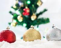bola de los chrismas del rojo, del oro y de la plata en nieve con vagos del árbol de los chrismas Fotos de archivo