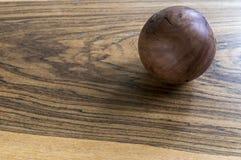 Bola de madeira em uma tabela de madeira no estúdio Fotografia de Stock Royalty Free