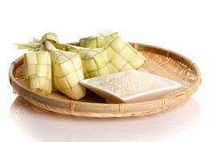 Bola de masa hervida del arroz de Ketupat y arroz en la bandeja tejida tradicional Imagen de archivo libre de regalías