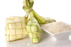 Bola de masa hervida del arroz de Ketupat y arroz en la bandeja tejida tradicional Imagenes de archivo