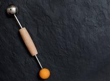 Bola de melão com baller do melão no fundo de pedra imagem de stock