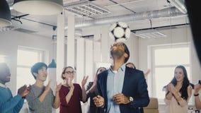 Bola de mnanipulação do CEO do afro-americano feliz na cabeça Os multi povos étnicos do executivo empresarial comemoram o sucesso video estoque