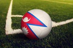 Bola de Nepal en la posici?n del retroceso de la esquina, fondo del campo de f?tbol Tema nacional del f?tbol en hierba verde imagen de archivo