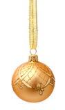 Bola de oro colgante de la Navidad con la cinta aislada Imagen de archivo libre de regalías