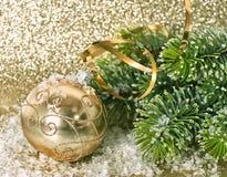 Bola de oro de la Navidad con la rama de árbol de navidad Foto de archivo
