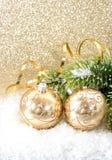 Bola de oro de la Navidad con la ramificación del árbol de navidad Imagen de archivo libre de regalías