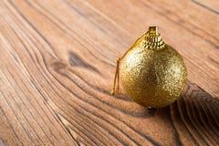 Bola de oro de la Navidad en el fondo de madera Foto de archivo libre de regalías