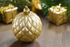 Bola de oro de la Navidad y ramas spruce en un fondo de madera Fotos de archivo libres de regalías