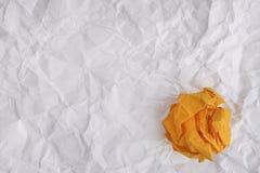 Bola de papel amarilla en fondo de papel arrugado Imagen de archivo libre de regalías