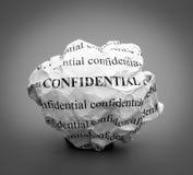 Bola de papel amarrotada com as palavras confidenciais no fundo cinzento Fotografia de Stock