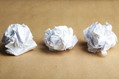 Bola de papel amarrotada em um fundo marrom Imagem de Stock