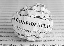 Bola de papel arrugada con las palabras confidenciales Foto de archivo