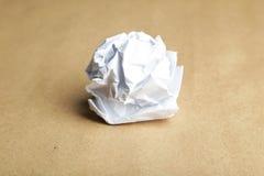 Bola de papel arrugada en fondo marrón Fotografía de archivo libre de regalías