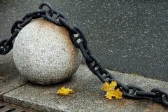 Bola de piedra con una cadena grande del metall, leav amarillo del arce del otoño dos fotografía de archivo