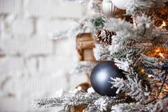 Bola de plata del juguete de la Navidad que cuelga en un árbol de navidad en el fondo de una pared de ladrillo blanca imagenes de archivo