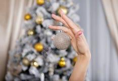 Bola de plata de la Navidad en una mano femenina, un decorat del árbol de navidad Fotografía de archivo