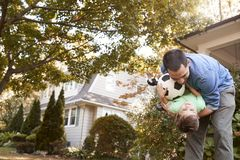 Bola de Playing With Soccer del padre en jardín con el hijo imagenes de archivo