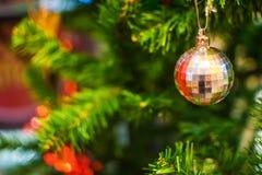 Bola de prata que pendura no ramo da árvore de Natal no fundo Imagens de Stock