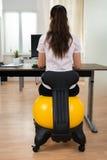 Bola de Sitting On Fitness de la empresaria en oficina Imágenes de archivo libres de regalías