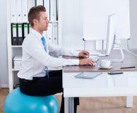 Bola de Sitting On Pilates do homem de negócios e computador da utilização Fotos de Stock Royalty Free