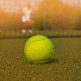 Bola de tênis e silhueta do jogador de tênis no sammer Imagens de Stock Royalty Free
