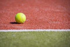 Bola de tênis em um campo alaranjado-verde Imagens de Stock
