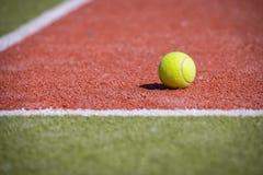Bola de tênis em um campo alaranjado-verde Imagem de Stock Royalty Free