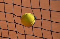 Bola de tênis na foto da rede do tênis Fotos de Stock