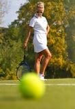 Bola de tênis no campo de tênis com o jogador no fundo Fotografia de Stock Royalty Free