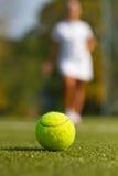 Bola de tênis no campo de tênis com um jogador borrado Foto de Stock Royalty Free