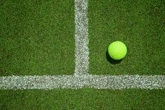 Bola de tênis perto da linha na corte de grama do tênis boa para o backgro Fotografia de Stock Royalty Free