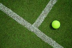 Bola de tênis perto da linha na corte de grama do tênis boa para o backgro Foto de Stock Royalty Free