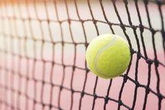 Bola de tênis que bate a rede do tênis no campo de tênis Fotos de Stock
