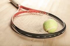 Bola de tênis que encontra-se na raquete em uma superfície de madeira Fotografia de Stock Royalty Free