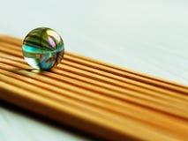 Bola de vidro no fundo de bambu das varas em um ângulo foto de stock royalty free