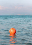 Bola de Waterpolo que flota en las aguas de mar Imagen de archivo libre de regalías