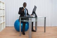 Bola de Working Sitting On Pilates del hombre de negocios Imagen de archivo