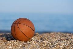 Bola del baloncesto que miente en la arena por el mar en la puesta del sol foto de archivo libre de regalías
