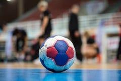Bola del balonmano en piso del ` s de la corte Árbitros, coches y atletas y fondo borrosos del campo Fotografía de archivo libre de regalías