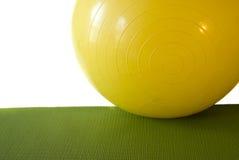 Bola del ejercicio en la estera del ejercicio Imagen de archivo libre de regalías