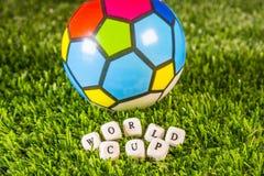 Bola del fútbol en hierba verde y palabras del mundial Foto de archivo